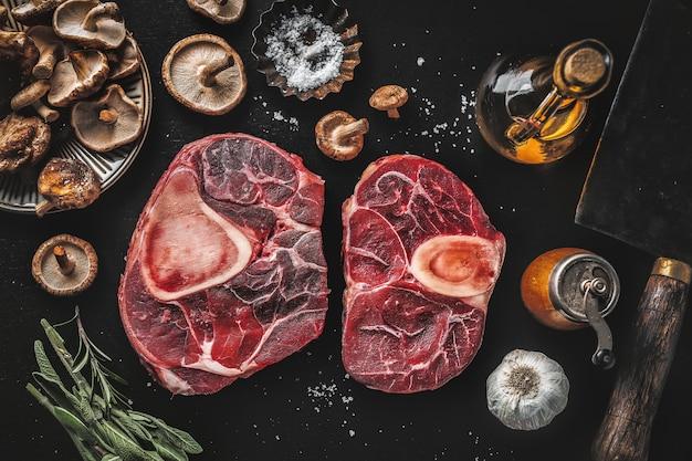 Сырое мясо с овощами и специями на темном столе. вид сверху.