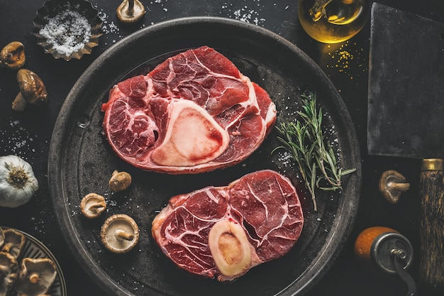 Сырое мясо с овощами и специями на темном винтажном фоне. вид сверху.