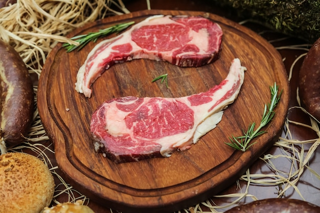 Raw meat on the wooden board with herbs
