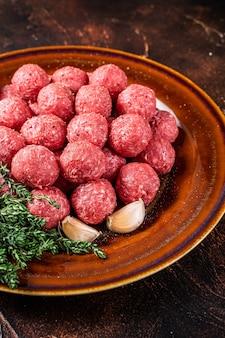 소박한 접시에 백리향과 다진 양고기 고기에서 생 미트볼. 어두운 배경입니다. 평면도.
