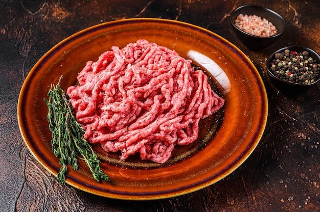Сырой фарш из говядины ангус вагю, фарш с зеленью на тарелке