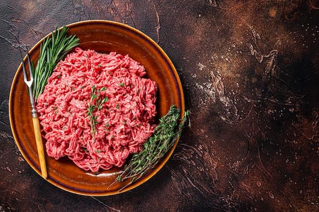 허브와 함께 소박한 접시에 원시 다진 쇠고기와 양고기. 어두운 배경입니다. 평면도. 공간을 복사합니다.
