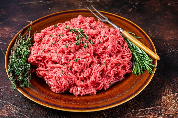Сырой фарш из говядины и баранины на деревенской тарелке с зеленью