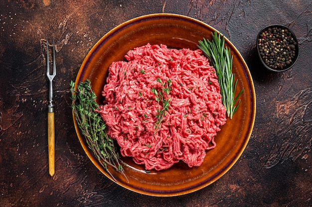 Raw mince beef and lamb meat on a rustic plate with herbs. dark background. top view.