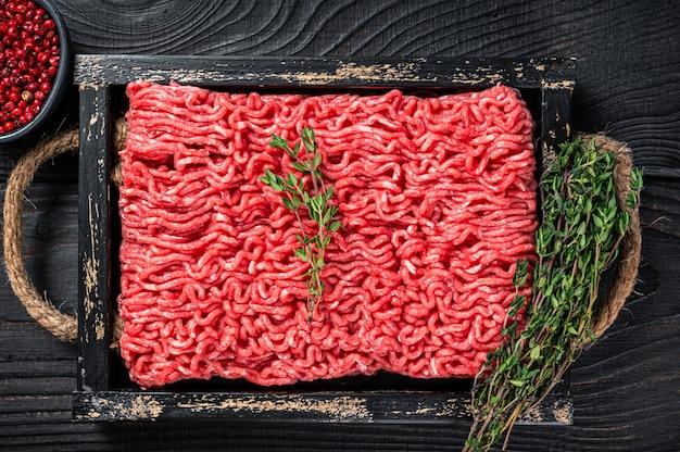 生のミンチ牛ひき肉と豚肉をハーブ入りの木製トレイに入れます。黒の背景。上面図。