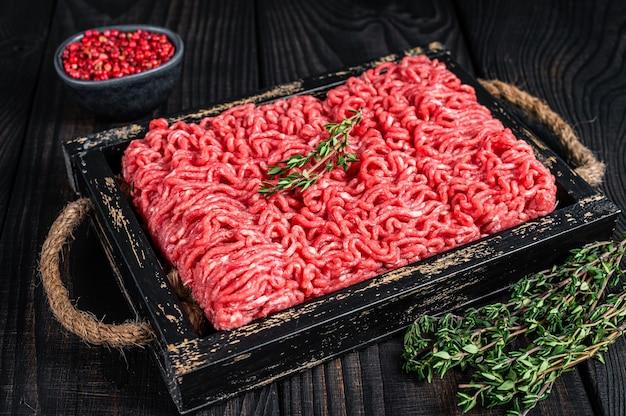 허브와 함께 나무 쟁반에 원시 다진 쇠고기와 돼지 고기. 검은 배경. 평면도.
