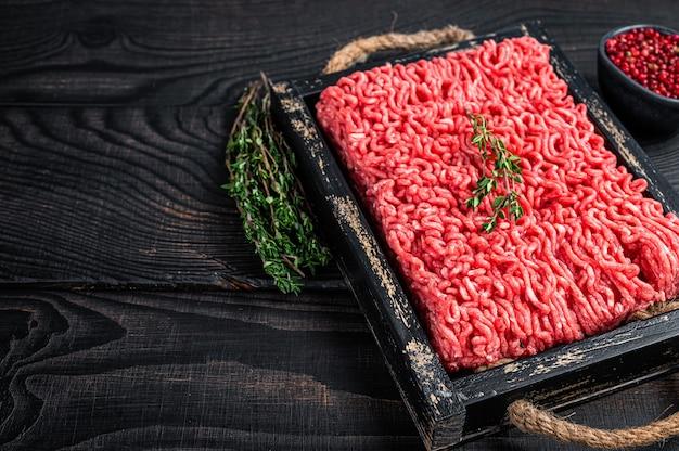 Сырой фарш из говядины и свинины на деревянном подносе с зеленью