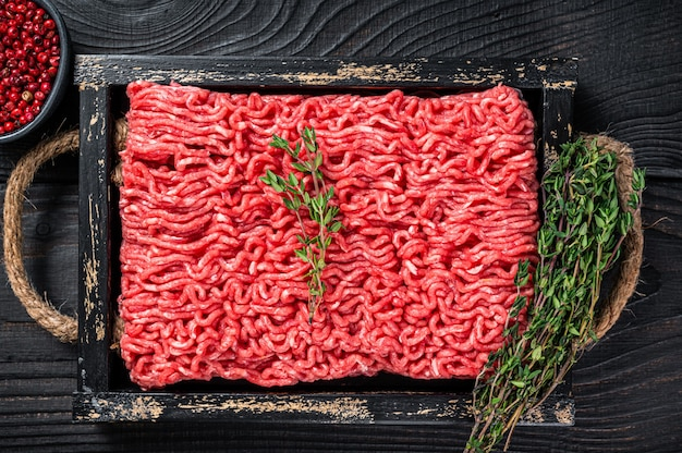 Raw mince ground beef and pork meat in a wooden tray with herbs. black background. top view.
