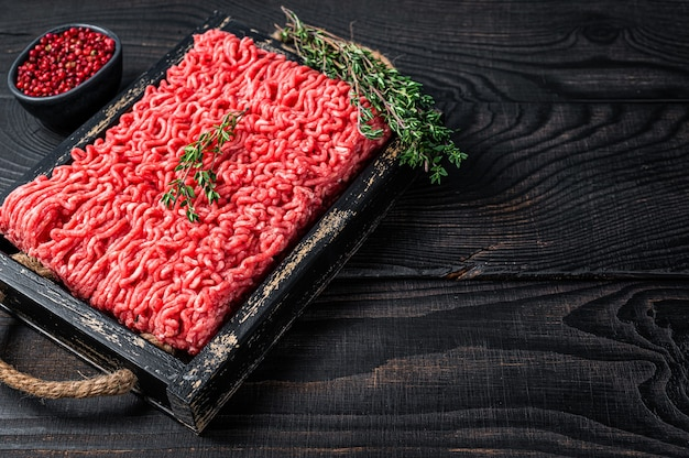 Raw mince ground beef and pork meat in a wooden tray with herbs. black