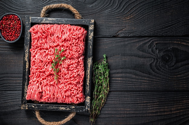 Raw mince ground beef and pork meat in a wooden tray with herbs