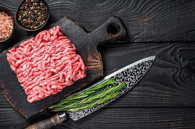 원시 다진 양고기, 나무 커팅 보드에 허브와 향신료를 넣은 갈은 고기. 검은 나무 배경. 평면도. 공간을 복사합니다.