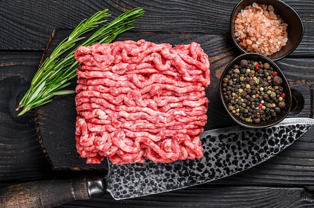 원시 다진 양고기, 나무 커팅 보드에 허브와 향신료를 넣은 갈은 고기. 검은 나무 배경. 평면도.
