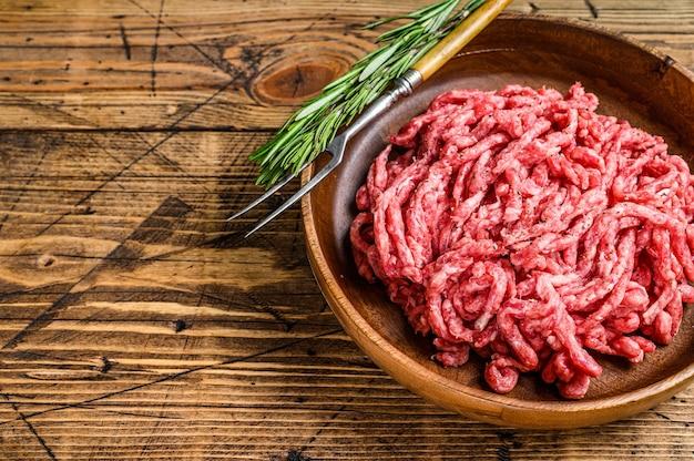 원시 말하다 양고기, 접시에 허브와 함께 갈은 양고기 고기. 나무 배경입니다. 평면도. 공간을 복사하십시오.