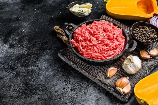 生のミンチ肉、にんにくと玉ねぎのカボチャ。黒の背景。上面図。スペースをコピーします。