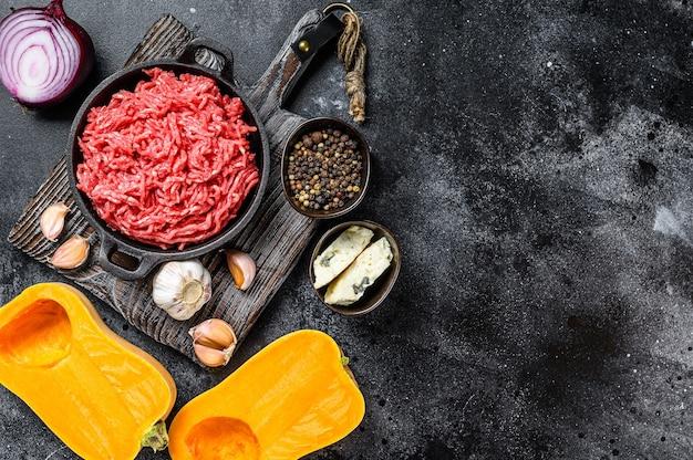 생 다진 고기, 마늘과 양파를 곁들인 호박. 검은 배경. 평면도. 공간을 복사합니다.