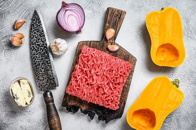 生のミンチ肉、にんにくと玉ねぎのカボチャ。白色の背景。上面図。スペースをコピーします。