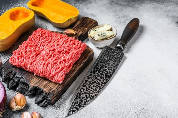 생 다진 고기, 마늘과 양파를 곁들인 호박. 흰색 배경. 평면도. 공간을 복사합니다.