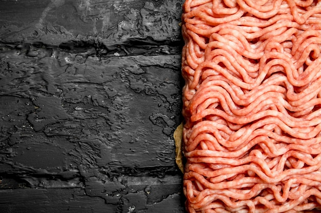 Raw minced beef . on black rustic background.