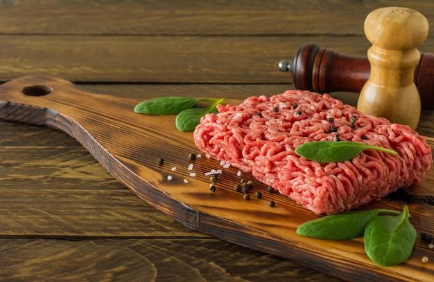 野菜とスパイスが入った木製のまな板に生の牛挽肉。料理と健康的な食事のコンセプト。