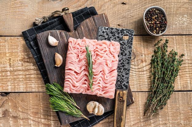 Сырой фарш из куриного мяса и индейки на деревянной разделочной доске с тесаком мясника. деревянный фон. вид сверху.