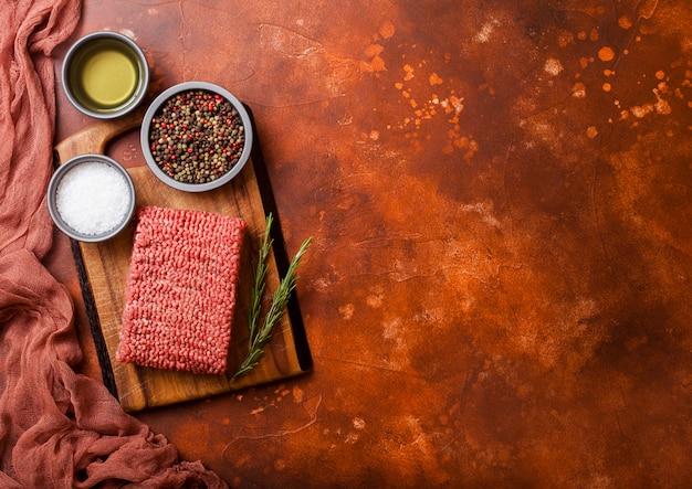 Сырой фарш домашнего говядины со специями и зеленью. вид сверху. поверх разделочной доски и ржавой кухни. с перцем, солью и чесноком.