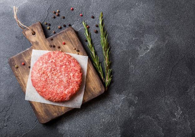 Сырой фарш домашний на гриле говяжий бургер со специями и зеленью. вид сверху. поверх разделочной доски и кухни.