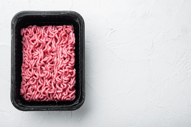 Raw minced meat in a black plastic container, on white