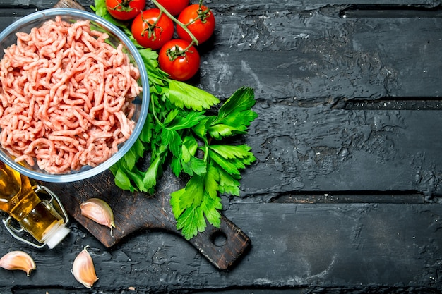 Raw minced meat in a bowl with green parsley and tomatoes.