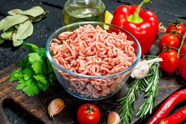 Raw minced meat in a bowl with vegetables and herbs. on black rustic background.