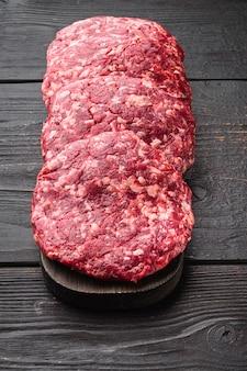 허브와 향신료 세트, 검은 나무 테이블에 원시 다진 고기 커틀릿