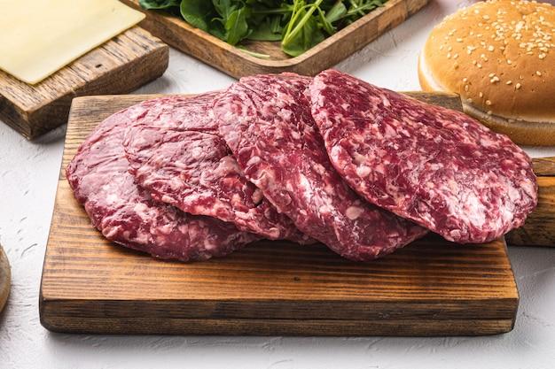 흰 돌에 허브와 향신료 세트와 함께 원시 다진 고기 커틀릿