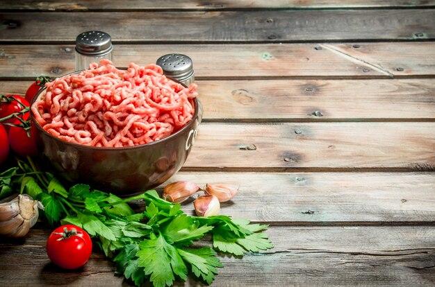 Сырой фарш в миске с петрушкой, помидорами и чесноком на деревенском столе.