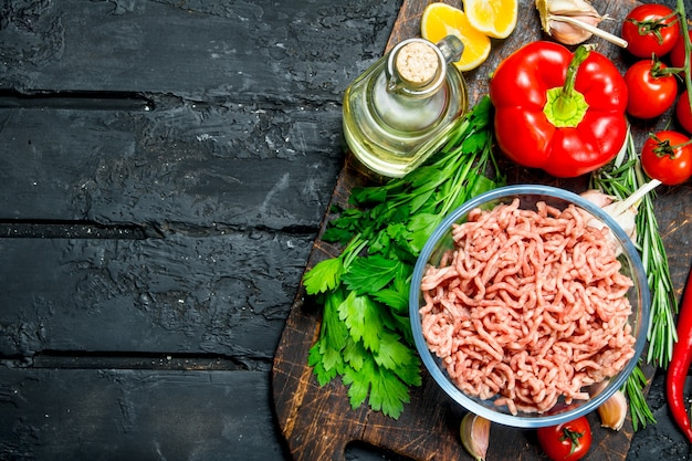야채와 허브 그릇에 생 다진 고기. 검은 소박한 배경.