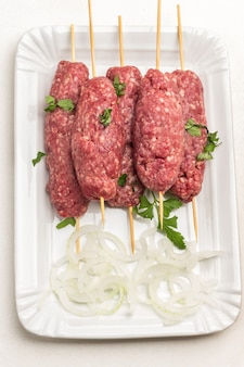 木製の串焼きに生のひき肉、白い皿に刻んだオニオンリング。白色の背景。フラットレイ