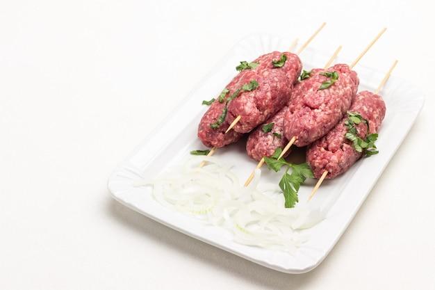 木製の串焼きに生のひき肉、白い皿に刻んだオニオンリング。白色の背景。