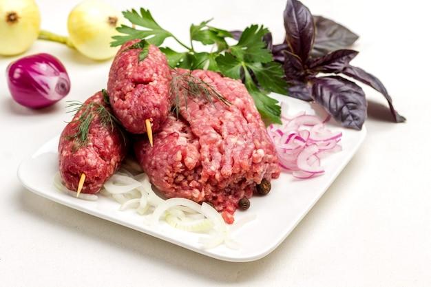 木製の串に刺した生のひき肉と玉ねぎを輪切りにしたもの。ケバブ料理。バジルの葉とタマネギの頭。白色の背景。