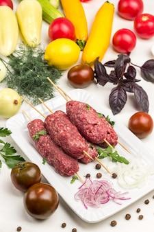 木製の串に刺した生のひき肉。トマト、ズッキーニ、ピーマン、ディル、バジルの小枝をテーブルに。白色の背景。
