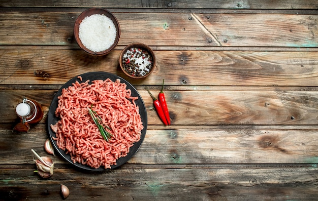 Raw minced meat in a plate with spices and herbs .