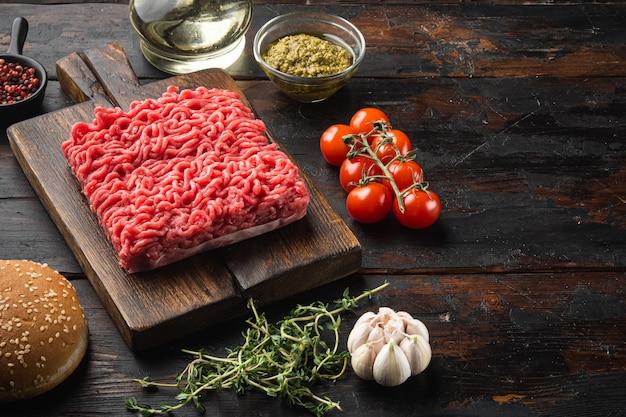 오래 된 어두운 나무 테이블에 나무 절단 보드에 미트볼 햄버거 세트 요리를위한 후추, 허브와 향신료와 원시 다진 고기