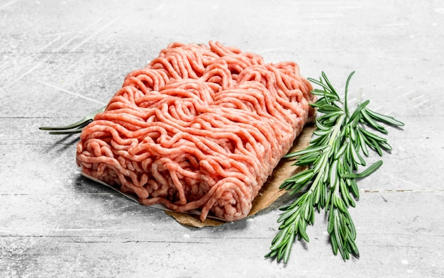 Raw minced meat with rosemary branches . on a rustic background.