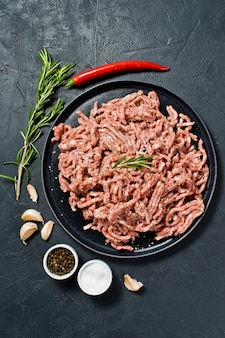 Raw minced on a stone board. ingredients for cooking, rosemary, chili pepper, garlic, salt.