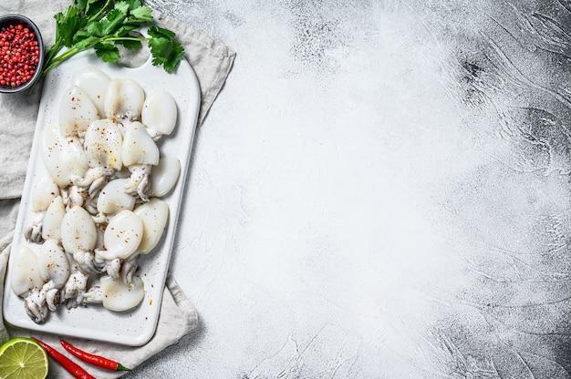Сырые мини-каракатицы с перцем чили и петрушкой на разделочной доске. серый фон