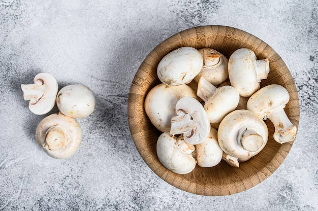 Raw mini mushroom champignon in a bamboo bowl. gray background. top view. space for text