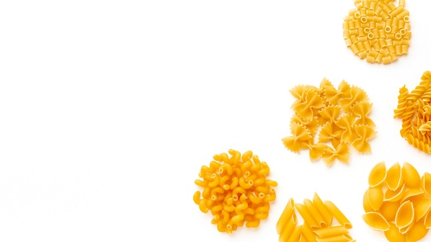 Raw mix of pasta on white background with copy space