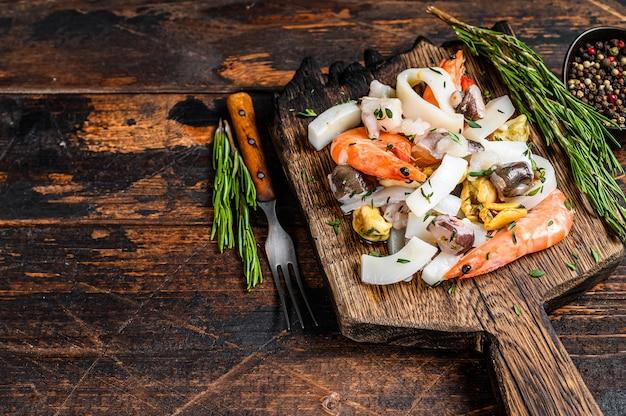도마에 새우, 새우, 홍합, 오징어, 문어와 함께 원시 믹스 해산물 칵테일. 어두운 나무 테이블. 평면도.