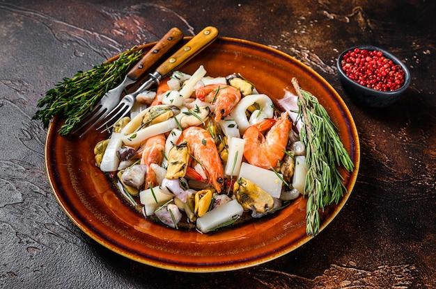 도마에 새우, 새우, 홍합, 오징어 및 문어와 함께 원시 믹스 해산물 칵테일