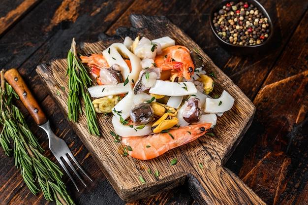 Сырой коктейль из морепродуктов с креветками, креветками, мидиями, кальмарами и осьминогами на разделочной доске.