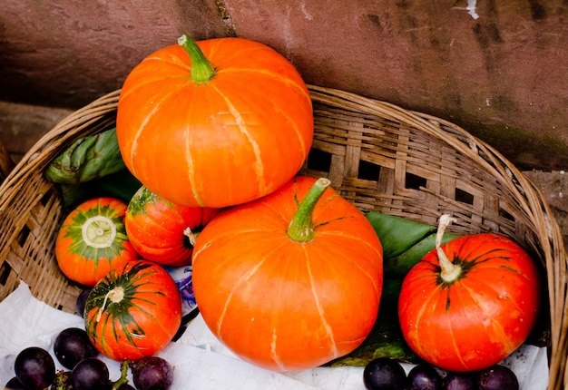 Raw multicolored pumpkins in bamboo basket