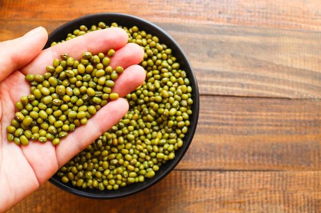 원시 녹두, 녹색 그램 또는 소녀의 손과 나무 배경에 접시에 으깬 콩