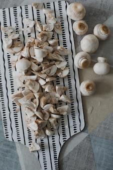 Сырые грибы шампиньоны на кухонном столе вид сверху еда фон